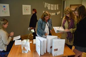 Eva Svensson tittar på Moa Lundholms teckningar tillsammans med Maria Viduss och Hanna Svensson.