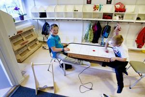 Nioåriga Elias Skoog och sexåriga Jack Alderborg spelar shufflepuck i klädrummet.