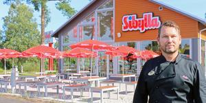Joakim Carlsson, 47, har varit vd på Sibylla sedan 2011. I bakgrunden syns restaurangen i Hofors som hade premiäröppet i torsdags.
