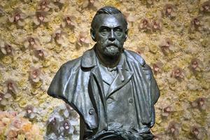 Byst av Alfred Nobel mot en fond av blommor inför Nobelprisutdelningen i Konserthuset i Stockholm . Bild: Claudio Bresciani/TT