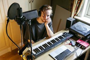 Med dator, keyboard och mikrofon gör Adam musik i sitt sovrum.