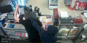 Med pistolen i höger hand trycker rånaren butiksbiträdet mot kassaapparaten och skriker att han inte ska titta upp. Sedan försvinner han springande från bensinmacken med bytet, 8000 kronor i kontanter. Bild ur polisens förundersökning