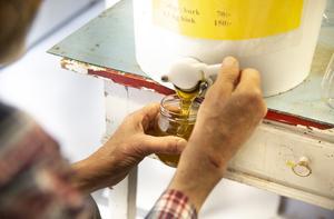 När honungen har silats klart kan John Bergström börjar fylla burkar och börja sälja.