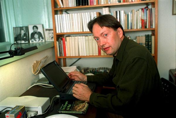 Horace Engdahl vid sitt skrivbord 1997. Vi hans sida ligger ett franskt exemplar a Charles Baudelaires klassiska diktverk