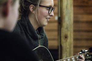 Emma Svensson tar fram gitarren för att ge lite exempel på ackordföljder och melodier.
