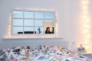 För att få sovrummet att upplevas större har de satt upp en fönsterspegel som sänggavel.