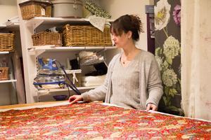 Lotta Bäck är tapetserare och driver sitt företag från en lokal i centrala Köping där hon både klär om möbler och syr gardiner och kuddar.