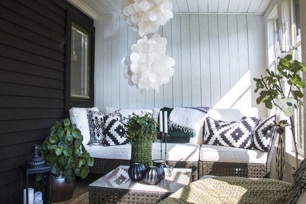 På den inglasade verandan har Anna inrett en mysig sittplats. Den ståtliga lampan av snäckskal har hon köpt i Thailand.
