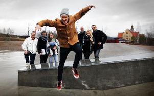 Falu Skate- och Snowboardklubbs ordförande Gustaf Wahlberg tar ett jätteskutt av förtjusning över att skateparken kommer att byggas ut. I bakgrunden Jonas Lennerthson, trafik- och fritids nämndens ordförande (S), Christian Hedman, Falu Skate, Elisabeth Ahnberg Åsenius, trafik och fritid (MP), Jonny Gahnshag, kommunstyrelsens ordförande (S), Linnea Risinger, kultur och ungdomsnämnden (MP) och Anders Nygårds, Falu Skate. Foto: Staffan Björklund
