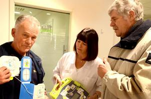 Gösta Ljungberg visar den nya hjärtstartaren för Marita Hedström och Lars Karlsson innan den sätts upp på apotekets vägg.