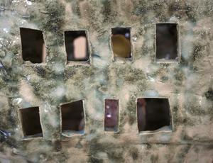 På utsidan är Joakim Tanos husskulpturer färgglada och roliga men inuti dem bor förvridna och sorgliga varelser som vi kan skymta genom fönster och glipor.
