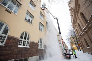 På Kyrkogatan är Martin Olsson högt upp i skyliftens korg och skottar bort snö från taket. På gatan håller Johanna Wängman koll på trafik och fotgängare.