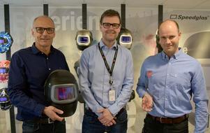 Anders Grönberg, Tomas Mattsson och Nichlas Sjöselius visar stolt upp en svetshjälm med nya och unika funktioner samt en av flera av de Red Dot-utmärkelser som företaget fått under senare år.