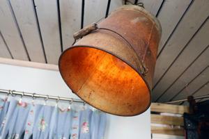 En rostig gammal hink har omvandlats till en taklampa som ger mysigt sken.