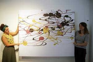 Nu har den kommit. Greta McMillans konstverk Griffin beach, som skapats med hjälp av ett dataprogram som läser av den 13-åriga konstnärens ögonrörelser. Laura Blake och Ellie Griffiths har just packat upp tavlan som inleder hela utställningen.