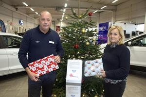 För varje julklapp som läggs under granen går 20 kronor till Röda korset. Per-Arne Arnberg (till vänster i bild) inspirerades till idén efter att ha läst om ett liknande koncept. Till höger i bilds syns Bilforum i Hedemoras ägare Britt-Marie Sahlander Arnberg