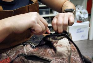 Linda Jonsson sprättar av blixtlåset på en jacka för att sätta dit ett nytt.
