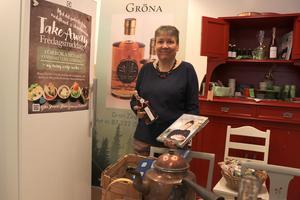 Eva Magnusson visar upp den nyligen utgivna boken med kaféer i Västernorrland - där bland annat hennes, som nu är till salu, finns med.