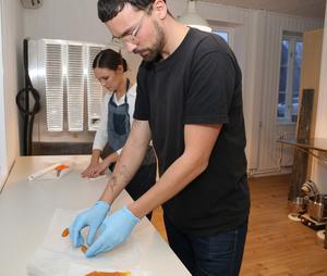 Alice Genberg och Ludvig Iraeus skär upp och packar apelsin- och saffranskola.