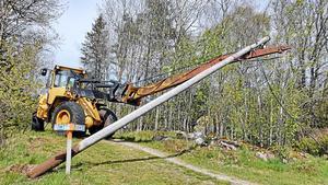 Sture Philipsson, 78 år, lägger försiktigt ner stolpen så att den inte ska skada Höglandsleden-skylten.