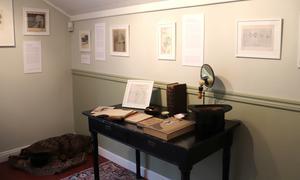 Mannens rum med skrivbord, hatt och teckningar.