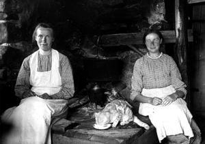Två okända kvinnor (och en katt) sittande på eldstad i Ulvsjön.