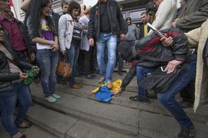 Trampar på landets  flagga. Proryska demonstranter hånar och trampar på den ukrainska flaggan.