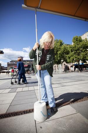 Nancy Åberg använder aldrig betongvikterna som hon fått av kommunen, men visar hur det är tänkt att de ska fungera. Trots att vikterna väger 15 kilo var kan det blir en sådan kraft i de segelstora markiserna att de lyfter vikterna en halvmeter upp i luften.