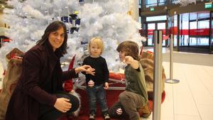 Renée Demark Lundgren, Stadsmissionen, hjälper Elliot och Liam Tingberg att hänga upp de första julkulorna.