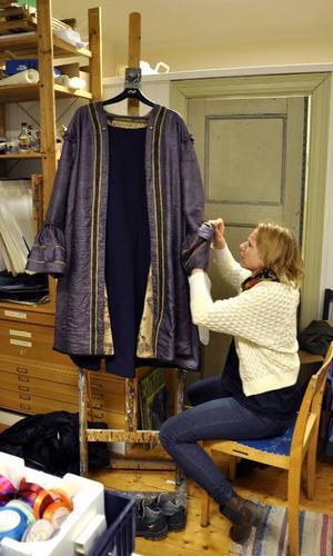 Avlagda gardiner kom väl till pass i kostymateljén. Malin Svelander visar detaljerna på rockärmen – gardinens hängen.