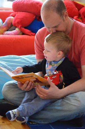 Petter Westergren läser saga med pappa Anders Westergren på Nora församlingshem.