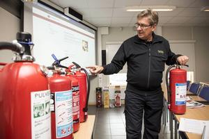 Arne Berggren visar upp ett antal olika typer av släckare. Låt er inte luras av behållarens storlek.
