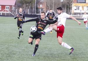 Strömsbergs mittback Björn Johansson i kamp med Hudiksvalls Cihan Sener.