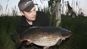 Andreas Kursu håller upp en av karparna han tog tidigare i sommar vid Melingssjön i Fagersta.