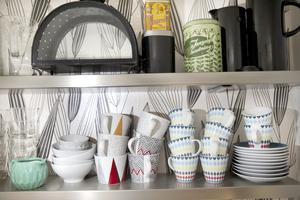 Muggarna med 50-talsinspirerat mönster står på öppna hyllor i köket.