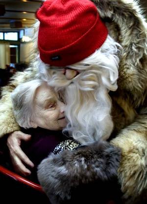 JULTOMTEN BESÖKTE FURUGÅRDEN. Anna-Lisa Hedlund kramade om tomten, Krister Larsson, rejält. Tomten var inbjuden av Väntjänsten. Han delade ut julklappar och sedan serverades kaffe och pepparkakor.