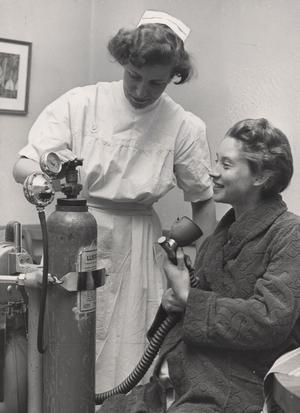 demonstrerar. Överbarnmorskan Anna-Brita visar blivande mamman Elsie hur hon ska använda lustgasen, år 1955. Lustgas var länge det enda smärtlindringen under förlossningen, men under 1950-talet dök det upp alternativ, och man både bedövade och påskyndade värkar på medicinsk väg.