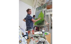Lisa Hedback från Halvarsgårdarna jobbar till vardags med konst - hon är modell - men har inget emot att måla.– Man får bra råd av Arne och Göran, berömmer hon.Foto: Hans Dahlqvist
