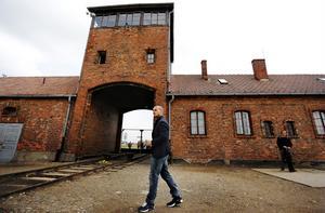 Besökare vid infarten till Auschwitz som den ser ut i dag.