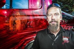 Chauffören Nicklas Nygren från Tudde Ghane´s åkeri på Gotland framför en av deras motivlackade asfalts lastbilar.