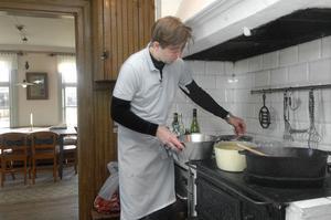 Melker Andersson bryner älgkött för 12 personer i en stor järngryta.