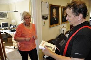 Sandra Lanner, mångårig kommunalrådssekreterare, får några böcker i gåvor som tack av Jens Nilsson. Och hon lovas också en lunch när hon hälsar på i Bryssel
