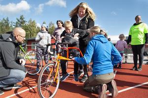 Wilgot, 8 år, får hjälp av mamma och Elin Lund Jonsson för att ta sig upp på cykeln.