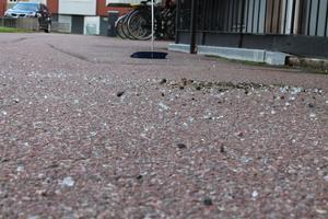 Glassplitter som fallit ned på gatan. Här är nästan allt sopat i en hög.