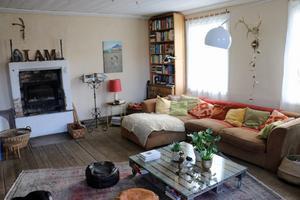 Vardagsrummet med ursprungligt trägolv och trätak och öppen spis där det numera finns en vattentank med ett system som värmer hela huset.