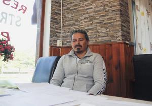 Framför sig på bordet har Mohamed Elnemrawi papper som visar dödsattesterna på nära släktingar, kopia av polisanmälan som gäller mordet på hans bror och en bild som visar kroppen efter hans mördade farbror.