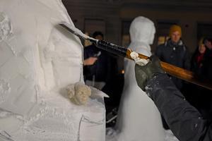 Nina jobbar koncentrerat med sin snöskulptur medan modellen av ansiktet vilar i skulptörens famn. Ett välkänt ansikte har börjat ta form.