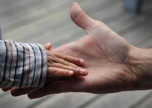 Barnhand i en vuxen hand. Foto. Hasse Holmberg/TT