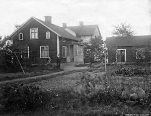 Här har vi Hjortstorpsvägen 41 på Norr. Bilden togs den 25 oktober 1919, då huset beboddes av familjen Johnsson. Sven Johnsson är den lille gossen, och han sitter på sin mamma Nancys arm. Svens pappa pappa Josef står bredvid. Foto: Örebro stadsarkiv