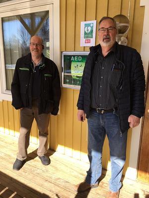 Håkan Söderlund tillsammans med bystugeföreningens ordförande, Thomas Hoonk, vid det nyinstallerade hjärtstartarskåpet som monterats i väggen på bystugan. Foto: Smedjebackens kommun